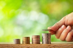 Рука кладя монетку на стог монеток с предпосылкой запачканной растительностью стоковое фото