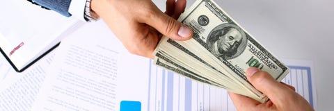 Рука клиента дает пакет 100 долларов счетов Стоковая Фотография RF