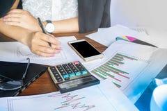 Рука коммерсантки анализируя запас и финансовая диаграмма сообщают с калькулятором, умным телефоном и тетрадью Стоковое Изображение RF