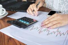Рука коммерсантки анализируя запас, финансовый отчет о диаграммы с калькулятором, умным телефоном Стоковые Изображения RF