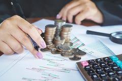 Рука коммерсантки анализируя на финансовой диаграмме с стогом монетки Стоковые Фотографии RF