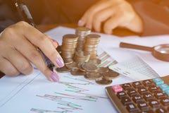 Рука коммерсантки анализируя на финансовой диаграмме с стогом монетки Стоковые Фото