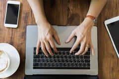 Рука коммерсантки взгляд сверху молодая используя компьтер-книжку на деревянном столе стоковые фото