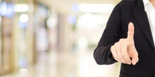 Рука коммерсантки касаясь над предпосылкой офиса нерезкости, делом Стоковая Фотография