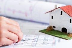 Рука конструируя план дома. Стоковое Изображение