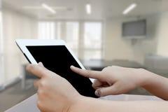 Рука конца-вверх используя цифровую таблетку на blured backgr конференц-зала Стоковое Изображение RF