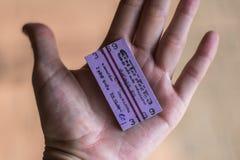 Рука конца-вверх человеческая в ладони лежит билет на поезд от Hikkaduwa к Unawatuna в Шри-Ланка стоковое фото