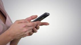 Рука красивой молодой женщины используя умный телефон на предпосылке градиента сток-видео