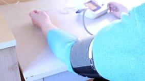 Рука кровяного давления пожилой женщины измеряя дома, тумак конца tonometer вверх акции видеоматериалы