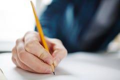 Рука крупного плана держа карандаш и рисовать Стоковое Изображение