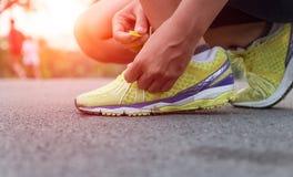 Рука крупного плана связывая шнурки готовые для бега на дороге Стоковое Изображение RF