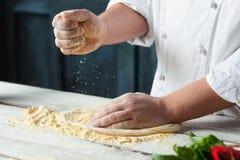 Рука крупного плана хлебопека шеф-повара в белой равномерной делая пицце на кухне Стоковые Изображения RF