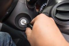 Рука кладя ключ автомобиля к keyhole Стоковые Изображения