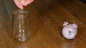 Рука кладя монетки в стеклянный опарник сток-видео