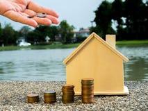 Рука кладя монетки денег штабелирует расти с домом позади, сохраняющ деньги для домашней концепции Стоковые Фото