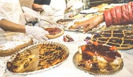Рука клиента выбирая кусок пирога на магазине кондитерскаи печенья Стоковая Фотография