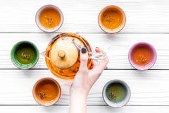 Рука льет чай от бака чая в чашки Белое деревянное взгляд сверху предпосылки Стоковое фото RF