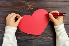 Рука любовного письма сочинительства девушки на день валентинки Handmade красная открытка сердца Женщина пишет на открытке для ce стоковая фотография rf