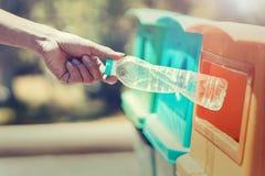 рука людей держа пластмассу бутылки отброса кладя в мусорную корзину для очищать стоковые фото