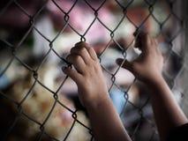 Рука маленькой девочки держа дальше загородку звена цепи для свободы, человеческую Стоковое Изображение