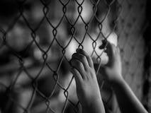 Рука маленькой девочки держа дальше загородку звена цепи для свободы, человеческую Стоковая Фотография