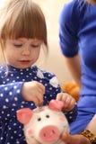 Рука маленькой девочки ребенка кладя монетки в piggybank Стоковое Изображение RF