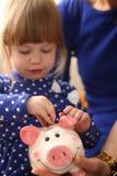 Рука маленькой девочки ребенка кладя монетки в piggybank Стоковые Фото