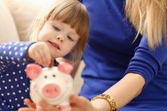 Рука маленькой девочки ребенка кладя монетки в piggybank Стоковое фото RF