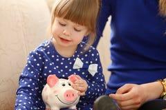 Рука маленькой девочки ребенка кладя монетки в piggybank Стоковая Фотография RF