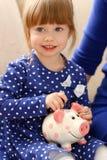 Рука маленькой девочки ребенка кладя монетки в piggybank Стоковая Фотография