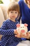 Рука маленькой девочки ребенка кладя монетки в piggybank Стоковые Изображения RF