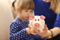 Рука маленькой девочки ребенка кладя монетки в piggybank Стоковые Фотографии RF