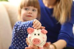 Рука маленькой девочки ребенка кладя монетки в piggybank Стоковое Фото