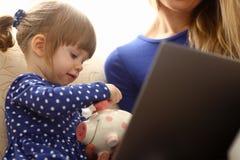 Рука маленькой девочки ребенка кладя монетку в piggybank Стоковые Изображения RF