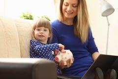 Рука маленькой девочки ребенка кладя монетку в piggybank Стоковые Фотографии RF