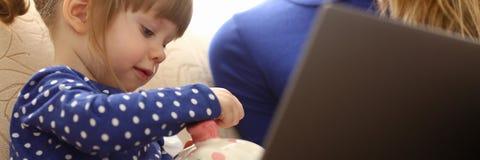 Рука маленькой девочки ребенка кладя монетку в piggybank Стоковые Фото