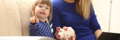 Рука маленькой девочки ребенка кладя монетку в piggybank Стоковое Изображение
