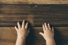 Рука малыша младенца на деревянном столе Стоковое Изображение RF