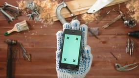 Рука мастера взгляд сверху в перчатке держа smartphone с зеленым экраном сток-видео