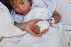 Рука матери держа больную руку дочери которое имеет решение IV перевязанное с любовью и заботой пока она лежит вниз на кровати стоковая фотография