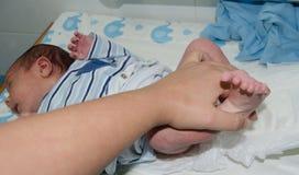 Рука матери изменяя newborn пеленку младенца на изменителе младенца стоковое фото