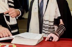 Рука мальчика читая еврейское Torah на бар-мицва Стоковая Фотография