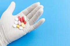 Рука медицинского работника в медицинских белых перчатках держа таблетку Стоковое Изображение RF