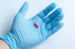 Рука медицинского работника в медицинских перчатках держа пилюльку Стоковые Фотографии RF