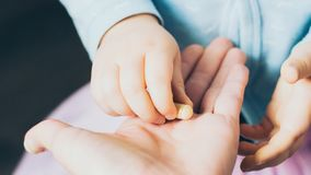 Рука младенца принимая пилюльку от взрослой руки ` s Стоковое Изображение