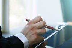 Рука молодого бизнесмена, подписывая контракт дела, конец-вверх подряд Стоковое фото RF