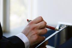 Рука молодого бизнесмена, подписывая контракт дела, конец-вверх подряд Стоковые Фото