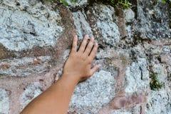 Рука молодой белой женщины касается стене касайтесь древности стоковое фото