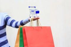 Рука молодой женщины держа голубую модельную миниатюрную корзину и кр стоковое фото rf