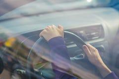Рука молодой женщины держа на черном руле пока управляющ в автомобиле взгляд от внешней стороны автомобиля стоковое изображение